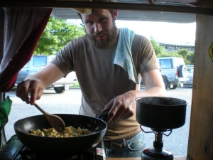 Tall man cooking food in the back of a hippie van - creating a good cooking set up is a big part of figuring out how to live in a van