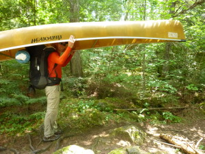 man in the BWCA carrying canoe and backpack in forest