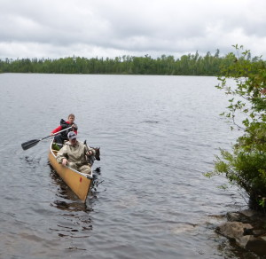 two woman in a canoe on a lake with dogs tipping the boat gunwales toward the water
