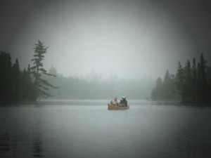 couple paddling in the BWCA canoe on lake surrounded by trees with dark grey skies and lots of mist/fog