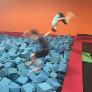 two people jumping off trampolines into foam pits