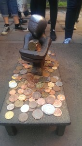 tiny metal figurine mounted on concrete and covered in wish coins