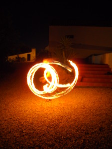 A fire twirler fire twirling seen by Half the Clothes Author Jema Patterson on her trip to Portugal