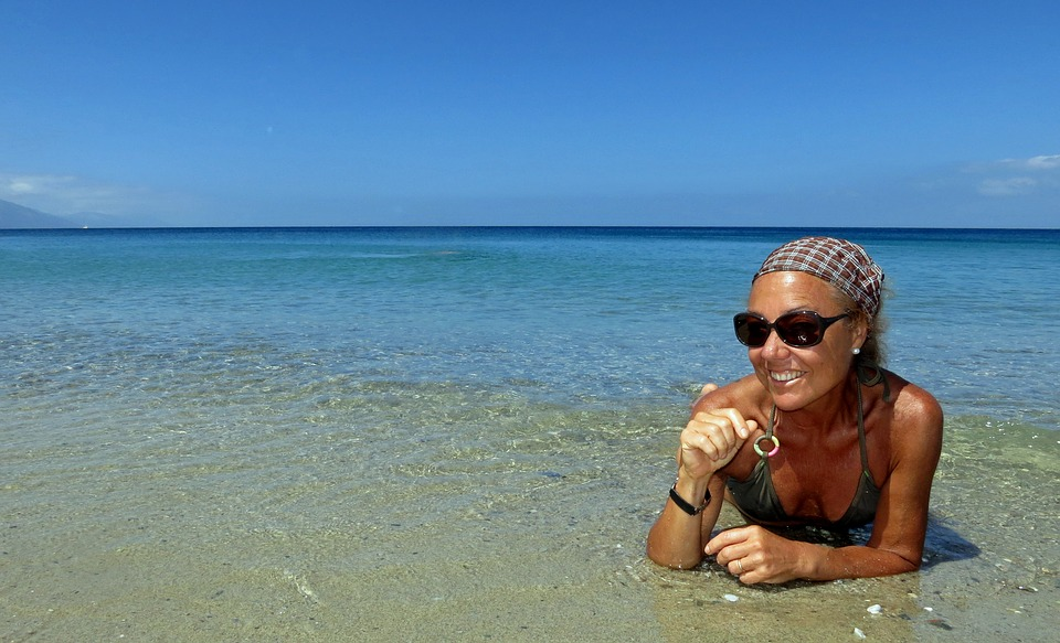 woman on beach sunbathing waiting to get a job while traveling the world