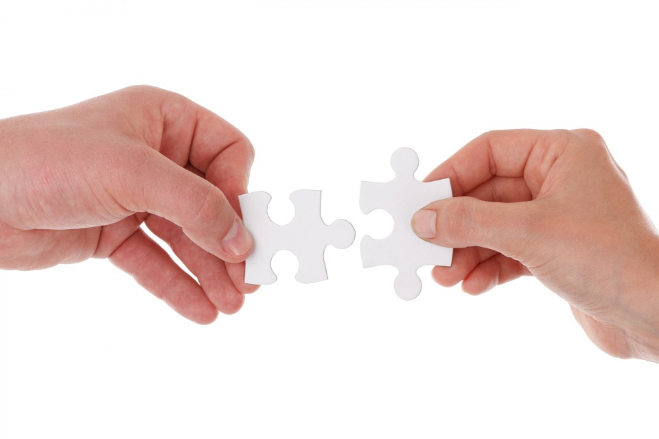 hands holding puzzle pieces that are about to connect just like budget travel blog Half the Clothes connects with other awesome things around the web