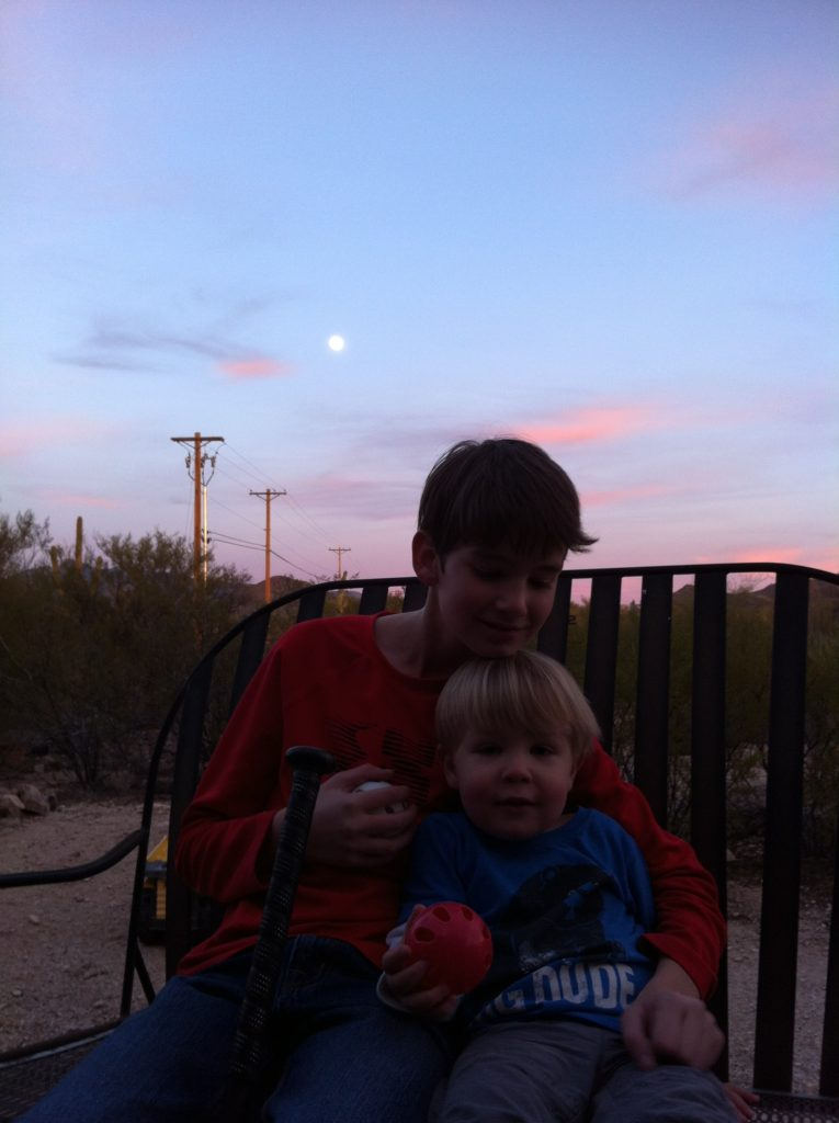 Top slow travel blog Half the Clothes author Jema playing baseball in the backyard on a full moon night with some of the littles in her life
