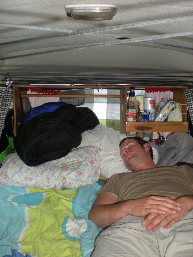 man sleeping in a van - how to live in a van - build a sleeping platform with storage underneath