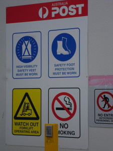 "An example of Australia's over-the-top safety culture. I saw this sign in an alley downtown outside the back door of the post office. Yes, to sort the mail you must wear a hi-visibility (""hi-vis"") safety vest and steel-toed boots."