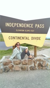 woman sitting under continental divide sign with mountains in background