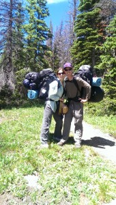 couple standing by a trail in the trees wearing hiking packs with an excessive amount of gear attached