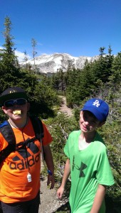 two boys in brightly colored tshirts standing on a nature trail with snowy and rocky mountains in background