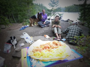 bwca meal - an open faced taco with campers sitting on rocks in the background and a lake and trees beyond