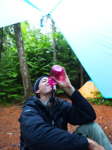 man sitting on ground in the BWCA (boundary waters canoe area) in the forest under a pale blue tarp drinking out of a pink bottle.