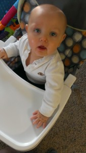 baby in high chair looking up at camera