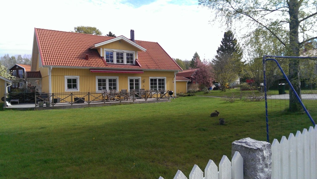 yellow swedish house with lawn and white picket fence