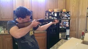 man aiming gun indoors rifle kitchen