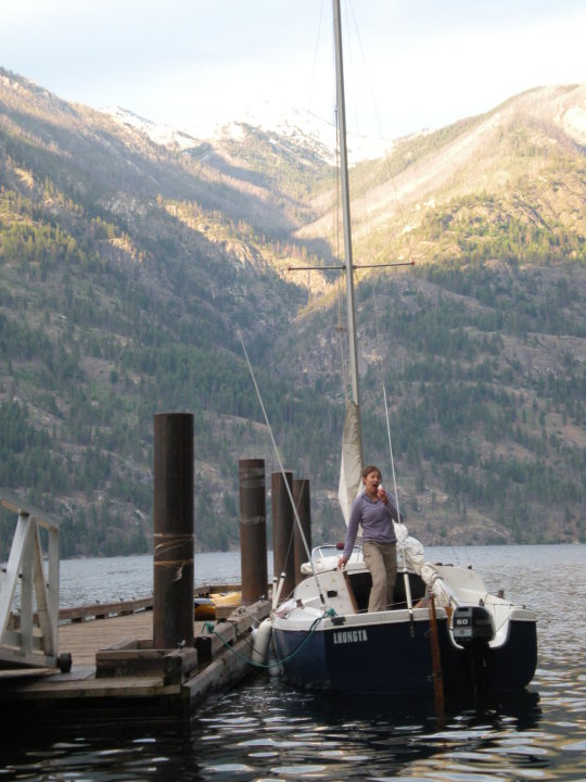 woman on sailboat at dock, mountains in background