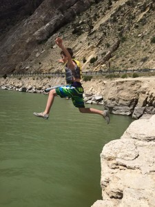 boy jumping off cliff making a leap taking a chance