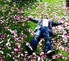 want to get a job while traveling the world? you could end up exhausted and laying on grass like this guy