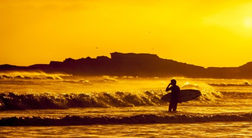 you, too, can go surfing at sunset if you have one of the best travel jobs to make money while traveling the world