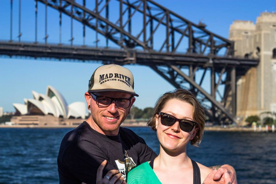 If you want to work in australia like this man and woman in front of the sydney harbour bridge and opera house, you should get an australia working holiday visa