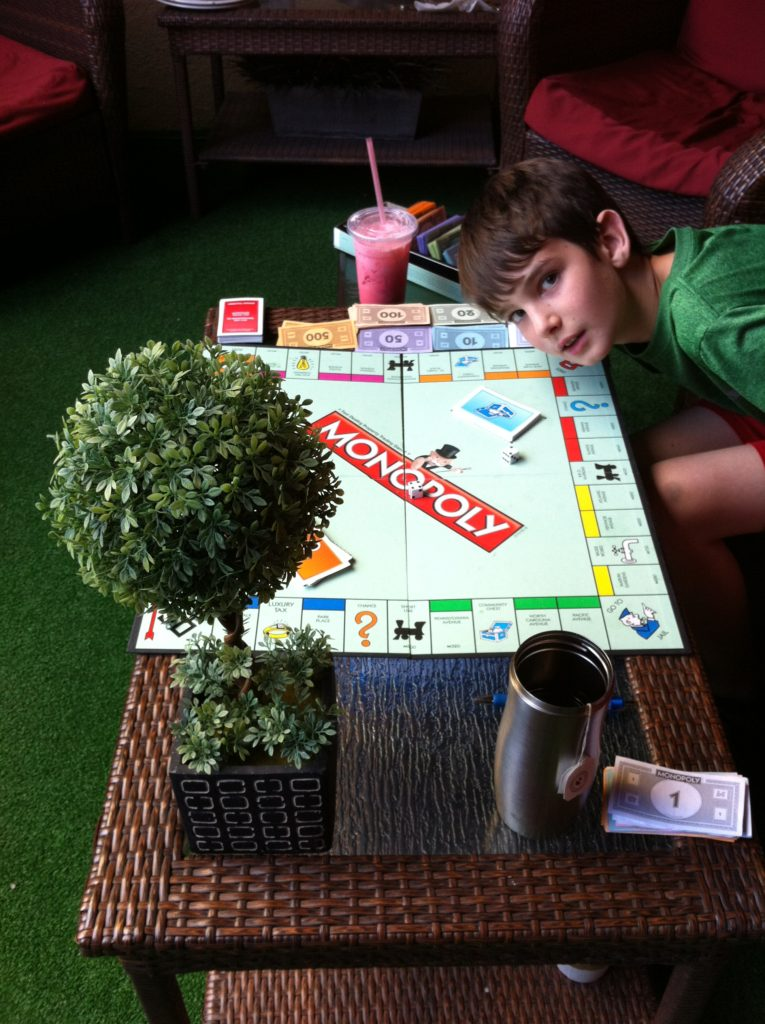Top slow travel blog Half the Clothes author Jema with her nephew playing board games at a coffee shop