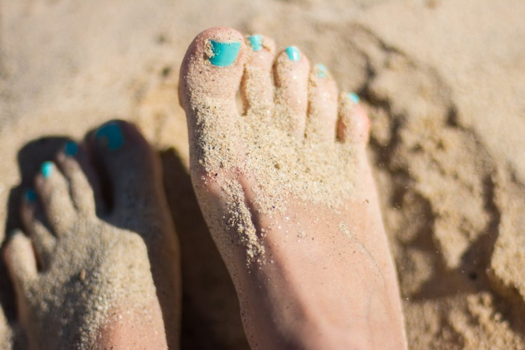barefoot runner feet covered in sand thinking about barefoot running benefits