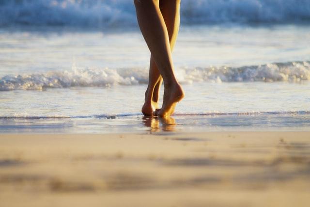 barefoot runner walks on beach thinking about barefoot running research