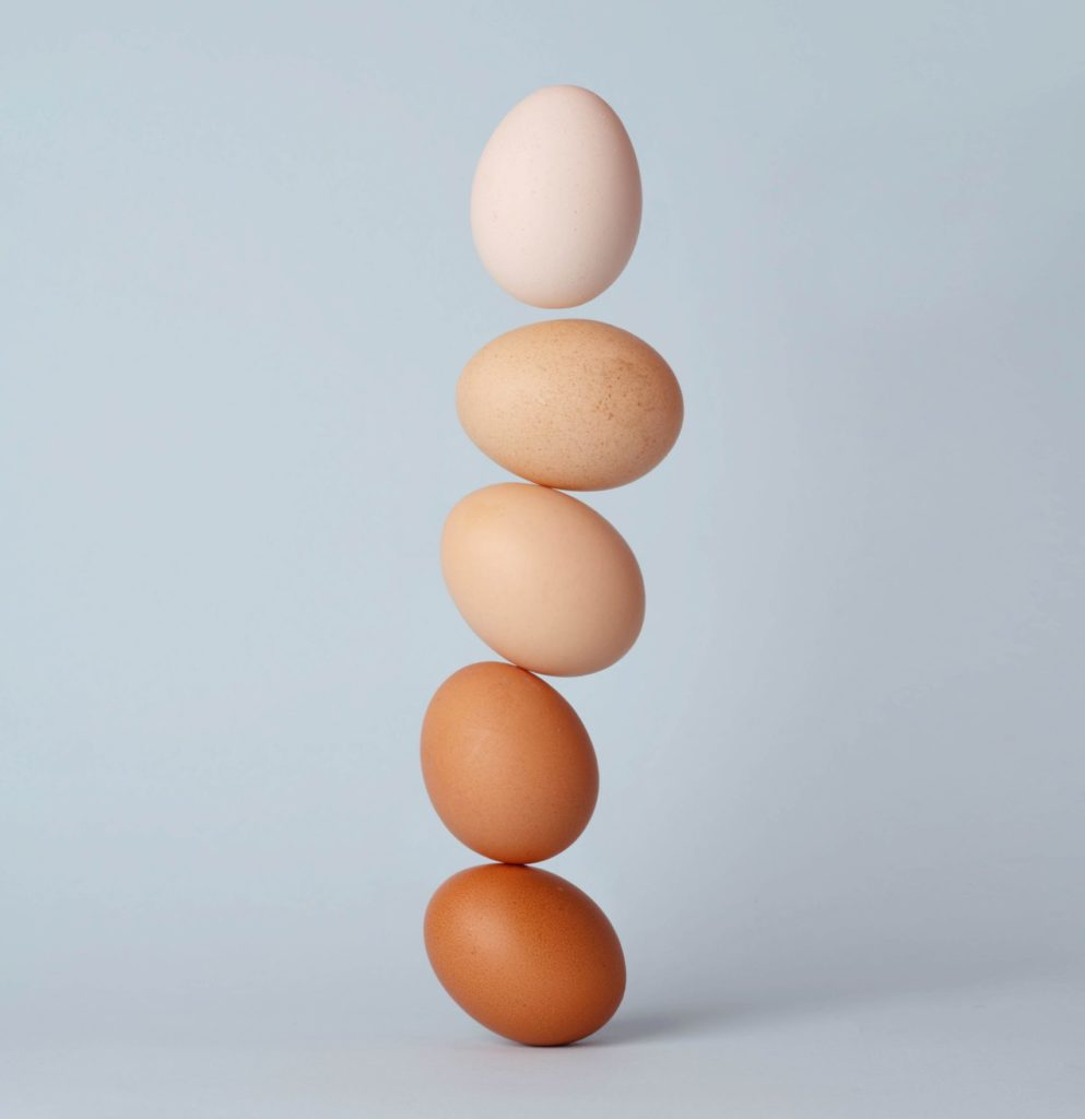 brown eggs precariously balanced in a stack - changing color in a gradient with brown on bottom and white on top